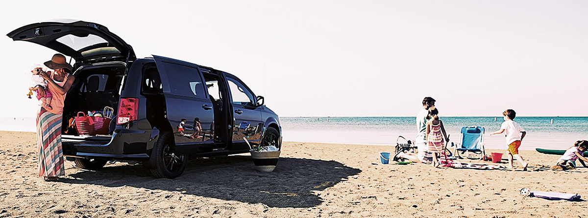A 2020 Dodge Grand Caravan parked on the beach with the sliding doors and liftgate open and a family unloading gear nearby.