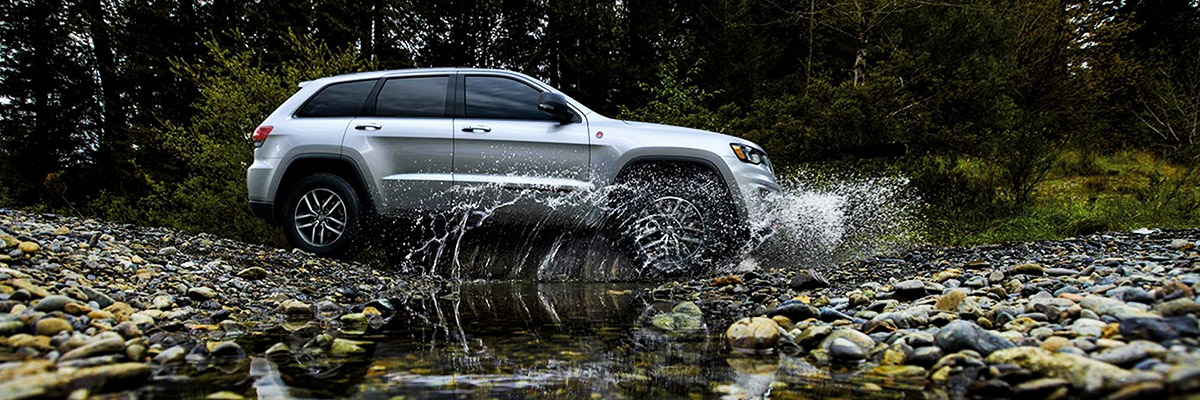 A silver 2020 Jeep Grand Cherokee Trailhawk spraying water from its wheels as it's driven through a stream.