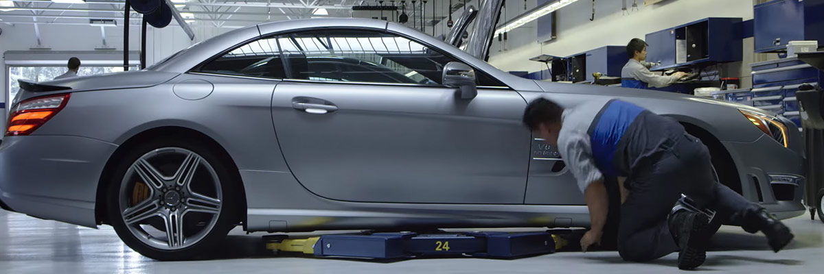 Mercedes-Benz auto mechanic peforming inspection under a mercedes sedan