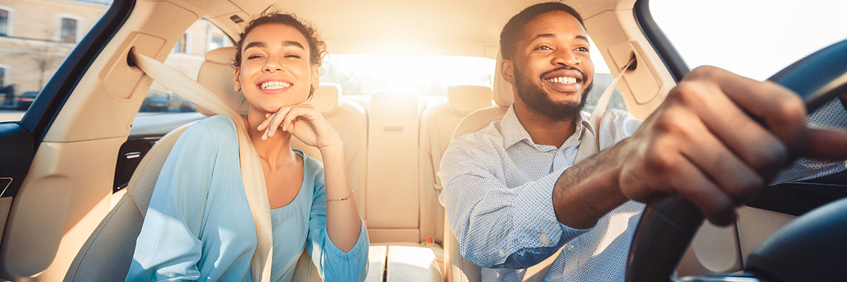 Young couple driving in their new car